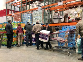 Shoppers stockpiling for COVID-19 grabbed for toilet paper as soon as a new pallet was available at the Deerfoot Heritage Costco in southwest Calgary on March 3, 2020. Stephanie Babych / Postmedia