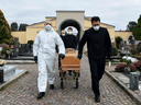 Pallbearers pull the coffin of a deceased person for a funeral ceremony into the cemetery of Grassobbio, Lombardy, Italy, on March 23, 2020, in the absence of quarantined relatives.