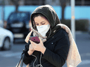 An Iranian woman wearing a protective mask checks a message on her smart phone in the Iranian capital Tehran on March 2, 2020, following the COVID-19 illness outbreak, which Iran says has claimed 66 lives.