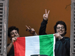 Men hold an Italian flag as they look out of an apartment window as part of a flashmob organized to raise morale during Italy's coronavirus crisis in Rome, March 13, 2020.