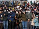 People wear protective face masks following the outbreak of the coronavirus disease (COVID-19) as they try to watch the Olympic cauldron during the Tokyo 2020 Olympic's Flame of Recovery tour at Ishinomaki Minamihama Tsunami Recovery Memorial Park in Ishinomaki, Miyagi prefecture, Japan March 20, 2020.
