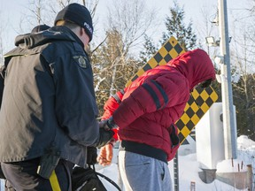 A young man from Yemen is handcuffed by an RCMP officer after crossing the border from the U.S. into Canada near Hemmingford, Que., on Friday, February 17, 2017. For many asylum-seekers, Roxham Road in the small Quebec town of Hemmingford represents the first steps of a potential new life.