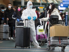 A air traveller is seen wearing a full Tyvek suit, protective goggles and a protective face mask as he waits to check in for his flight at Vancouver International Airport in Richmond, B.C. Wednesday, March 18, 2020.