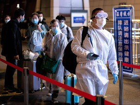 Passengers wear hazmat suit as they arrive at the Wuhan Wuchang Railway Station in Wuhan, to leave the city in China's central Hubei province early on April 8, 2020. (NOEL CELIS/AFP via Getty Images)