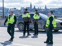 Quebec Provincial Police checking for drivers and passengers possibly infected with COVID-19 stop vehicles on the Macdonald-Cartier Interprovincial Bridge on Wednesday as they entered Gatineau from Ottawa.