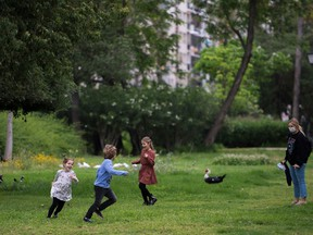 Children run under the eye of her mother as they play in a park on April 26, 2020 amid a national lockdown to prevent the spread of the COVID-19 disease.