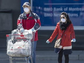 A couple wearing masks leave Markham's Denison Centre with groceries during the ongoing  pandemic, Wednesday April 1, 2020.