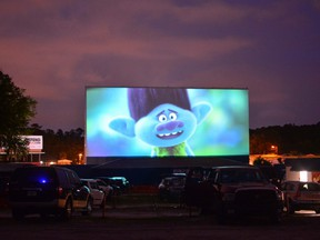 people watch the movie Trolls from their cars, separated from other cars by a 10-foot orange fencing in an effort to respect social distancing amid the novel coronavirus pandemic, at the Ocala drive-in theatre in Ocala, Florida