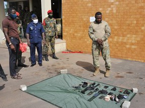 The man arrested in Accra, Ghana, for impersonating a Canadian Armed Forces officer is seen in uniform in front of guns and other items police said he carried.