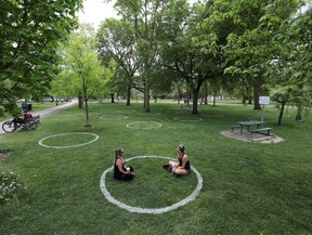 Women sit in a field where circles were painted to help visitors maintain social distancing to slow the spread of COVID-19 at Trinity Bellwoods park in Toronto, Ontario, May 28, 2020.