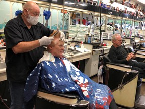 Barber Tommy Thomas, 69, who has been cutting hair for 50 years, gives his long-time customer Fred Bentley a haircut after the Georgia governor allowed a select number of businesses to open during the coronavirus disease (COVID-19) restrictions in Atlanta, Georgia, U.S. April 24, 2020.