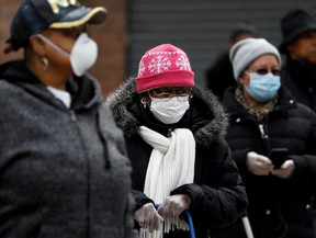People wearing protective masks wait in line for donated food distribution at the Queensbridge Houses, a New York City Housing Authority public housing complex,  in the Queens borough of New York, U.S., April 21, 2020.