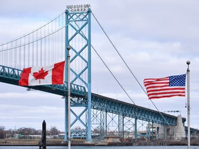 Canadian and American flags fly near the Ambassador Bridge at the Canada/USA border crossing in Windsor, Ont. on March 21, 2020.