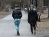 Two women ignore social distancing as they walk at Lafontaine park in Montreal on April 1, 2020.