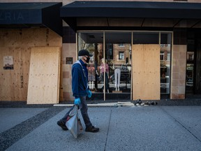 A man wearing latex gloves and a fabric mask on his face walks past a clothing store being boarded up, in Vancouver, on Thursday, April 16, 2020.