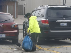 A worker scoops up latex gloves, tossed away by shoppers before getting into their vehicles, in the parking lot at a Metro grocery store at Eglinton Ave. E. and Markham Rd. in Scarborough on Wednesday, March 25, 2020.