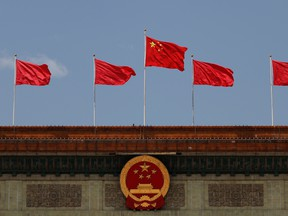 A Chinese flag flutters above the Chinese national emblem at the Great Hall of the People after the opening session of the National People's Congress in Beijing on May 22.
