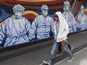 A man wearing a protective face mask walks past a mural of heath care workers painted on a boarded up restaurant in downtown Vancouver, Monday, April 27, 2020.