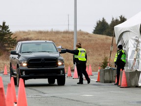 A Nova Scotia conservation officer passes a paper to a person crossing into the province from New Brunswick in its effort to prevent the spread of the coronavirus disease at the Fort Lawrence, Canada April 2, 2020.