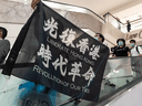 A pro-democracy supporter holds a Liberate Hong Kong. Revolution of Our Time flag during a rally at a shopping mall on May 25, 2020 in Hong Kong.