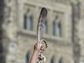 An eagle feather is held up during a rally for Missing and Murdered Indigenous Women and Girls on Parliament Hill in Ottawa on October 4, 2016. With reports of a sharp rise in violence against Indigenous women as COVID-19 restrictions keep families stuck in their homes, concerns are being raised about whether the pandemic could delay the promised June delivery of a national action plan on missing and murdered Indigenous women. The Native Women's Association of Canada has been conducting a series of nation-wide, grassroots consultations with their local member offices and with Indigenous women to determine how COVID-19 has been affecting First Nations, Inuit and Metis women in Canada.