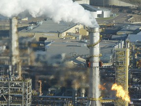 A stack belches smoke and a flare burns off gas at the Syncrude upgrader plant near Fort McMurray, Alta., in 2006.