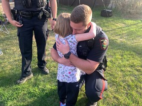 Const. Michael Norrie with the Prince Albert Police Service gets a warm hug from Kendra in Prince Albert, Sask. on Tuesday, May 19, 2020. Kendra, a five-year-old girl who survived when her paternal grandparents and brother died in a triple slaying in Saskatchewan, came home to a welcome that astonished and delighted her.THE CANADIAN PRESS/HO-Nigel Maxwell, paNOW MANDATORY CREDIT