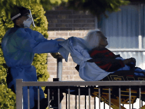 Patients are transported at the Orchard Villa Retirement Residence on April 22, 2020 following a deadly COVID-19 outbreak.