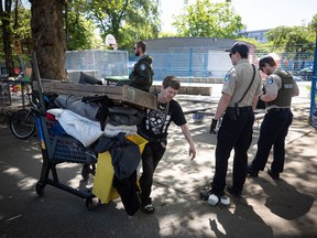 Park rangers stand by as Kim Berg moves her belongings out of a homeless camp at Oppenheimer Park just before a 12 p.m. deadline for the park to be vacated, in the Downtown Eastside of Vancouver, on Saturday, May 9, 2020. Vulnerable and homeless people across British Columbia could soon receive a smartphone to access support services and to stay connected with friends and family while practising physical distancing.