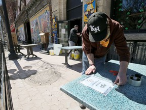 An employee at the King's Head Pub in Winnipeg prepares a patio for patrons. Calgary should allow the expansion of patios, even on to streets, during the better weather to help establishments get back on their feet, says columnist Rob Breakenridge.