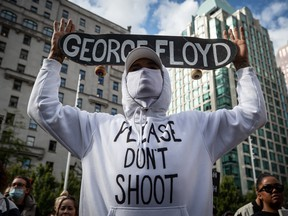 A man holds a skateboard bearing George Floyd's name above his head as thousands of people gather for a peaceful demonstration in support of Floyd and Regis Korchinski-Paquet and protest against racism, injustice and police brutality, in Vancouver, on May 31.