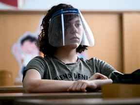 A student wears a face shield in Pristina, Kosovo, on June 9, 2020, as schools gradually reopen after almost three months of restrictions due to the COVID-19 pandemic.  Eye protection is typically under-considered and can be effective in community settings according to a review that synthesized all available evidence on physical distancing, face masks and eye protection.