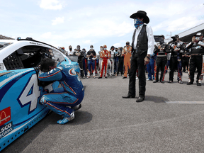 Bubba Wallace, driver of the #43 Victory Junction Chevrolet, kneels as team owner, and NASCAR Hall of Famer Richard Petty and NASCAR drivers stand in solidarity with Wallace prior to the NASCAR Cup Series GEICO 500 on June 22, 2020 in Talladega, Alabama.