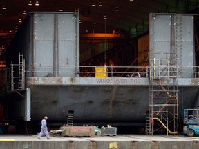 A Seaspan Vancouver Shipyards worker walks past a barge under construction in North Vancouver, B.C., on Wednesday November 2, 2011.