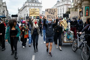 Demonstrators hold banners as they march during a Black Lives Matter protest near Piccadilly Circus in London, on June 29. Those who ask why protesters are in the streets, here is your answer: the slow drip of systematic racism, writes  Lloyd Wilks.