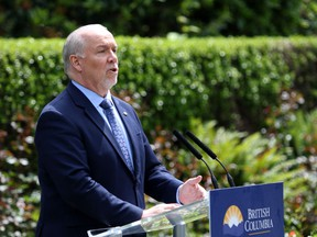 B.C. Premier John Horgan provides the latest update on the COVID-19 response in the province during a press conference from the rose garden at Legislature in Victoria, B.C., on Wednesday, June 3, 2020. Horgan says those who have offshore licence plates on their vehicles while driving in the province should take the bus or ride a bicycle if they're feeling harassed by the public.
