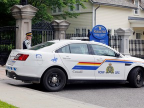 A police officer guards the front gate to Rideau Hall, and the grounds where Prime Minister Justin Trudeau lives, after an armed man was apprehended on the property, on July 2.