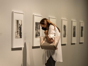 A patron wearing a mask looks closely at photographic work by Diane Arbus at Toronto's Art Gallery Of Ontario, August 20, 2020.