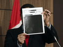 Conservative MP Pierre Poilievre holds up redacted documents related to the WE scandal, tabled at the House of Commons finance committee by the Liberal government, Wednesday, Aug. 19, 2020.