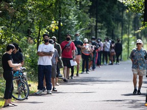 People wait in line at a COVID-19 testing facility in Burnaby, B.C., on Thursday, August 13, 2020. A new public opinion study suggests Canadians believe the COVID-19 crisis has brought their country together, while Americans blame the pandemic for worsening their cultural and political divide.