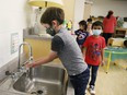 A kindergarten student wears a mask and washes his hands prior to a nutrition break at MacLeod Public School in Sudbury, Ont. on Tuesday September 8, 2020.