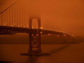 "Cars drive during midday along the Golden Gate Bridge in San Francisco under an orange smoke-filled sky on September 9, 2020.  More than 300,000 acres are burning across the northwestern state including 35 major wildfires, with at least five towns ""substantially destroyed"" and mass evacuations taking place."