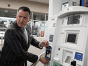 Ontario Energy Minister Greg Rickford applies an anti-carbon tax sticker to a gas pump, April 8, 2019.