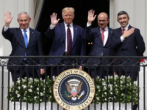 Israeli Prime Minister Benjamin Netanyahu, from left, U.S. President Donald Trump, Bahrain Foreign Affairs Minister Abdullatif bin Rashid Al Zayani and UAE Foreign Affairs Minister Abdullah bin Zayed Al Nahyan wave from a White House balcony after signing the Abraham Accords on Sept. 15, 2020.