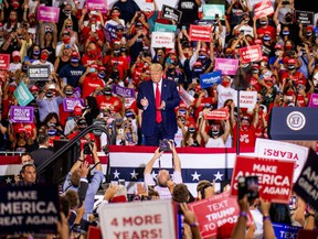 U.S. President Donald Trump, center, claps during a campaign rally at Xtreme Manufacturing's warehouse in Henderson, Nevada, U.S., on Sunday, Sept. 13, 2020.
