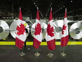 Canadian flags stand in front of rolls of coated steel at Stelco in Hamilton