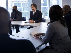 Prime Minister Justin Trudeau sits alongside HXOUSE co-founder Ahmed Ismail, as he meets with Black entrepreneurs at HXOUSE in Toronto, Wednesday, Sept. 9, 2020.