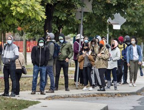 People wearing masks wait in line for Covid-19 Testing at Toronto's St. Joseph's Health Centre during the Covid-19 pandemic, Friday October 2, 2020.