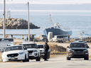 RCMP officers monitor the entrance to Saulnierville Harbour while in the background another checkpoint is being maintained, as non-Indigenous commercial fishermen protest against a Mi'kmaq lobster fishery in Nova Scotia, October 19, 2020.