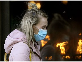 A woman wears a face mask while walking in downtown Edmonton on Wednesday, Nov. 4, 2020.